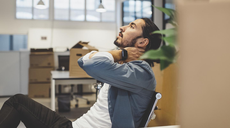 Die Verspannung im Nacken massiert sich ein junger Mann, der auf einem Bürostuhl sitzt, einfach weg