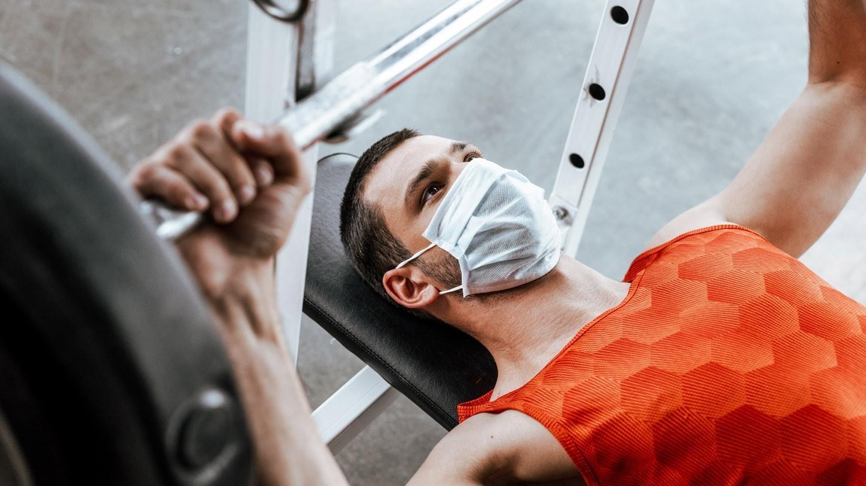 Sport mit Maske: Junger Mann mit Mund-Nasen-Maske liegt auf Trainingsbank und stemmt Hantel.