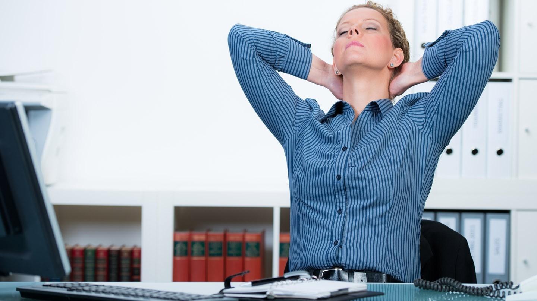 Nackenverspannung lösen: Junge Frau am Schreibtisch lehnt sich mit im Nacken verschränkten Armen und geschlossenen Augen nach hinten.