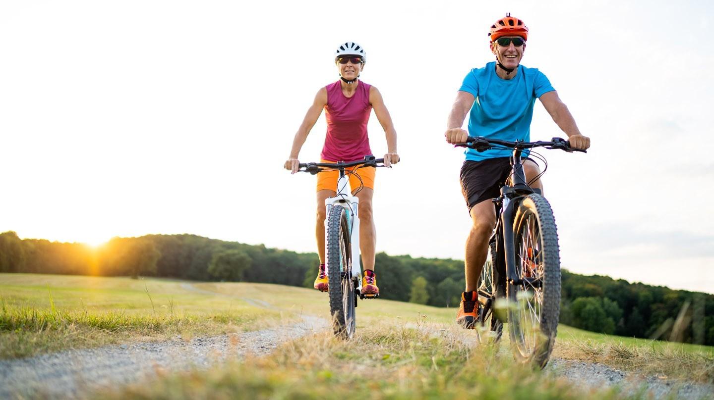 Mit Sport die Abwehrkräfte stärken: Eine Frau und ein Mann fahren mit Mountainbikes über einen Schotterweg.