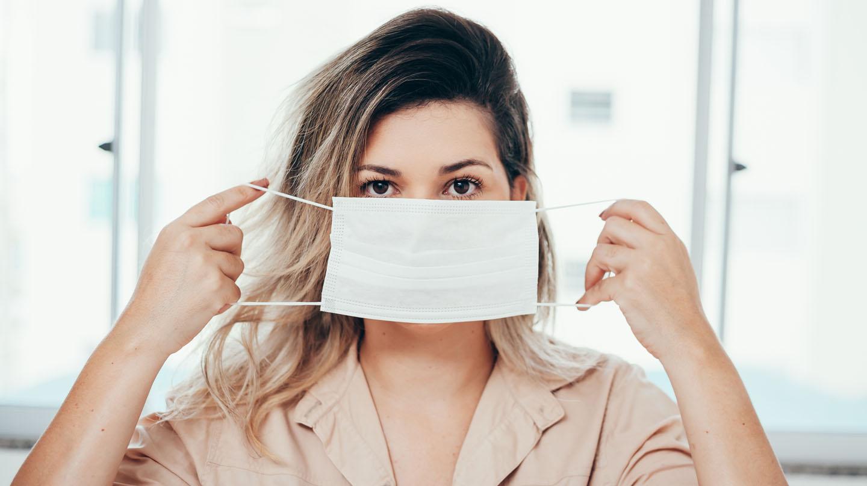 Maskne: Junge Frau hält eine Mund-Nasen-Maske an den Haltegummis vor dem Gesicht.