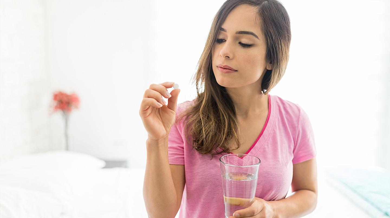 Pille danach: Junge Frau schaut kritisch auf die Tablette in ihrer Hand.